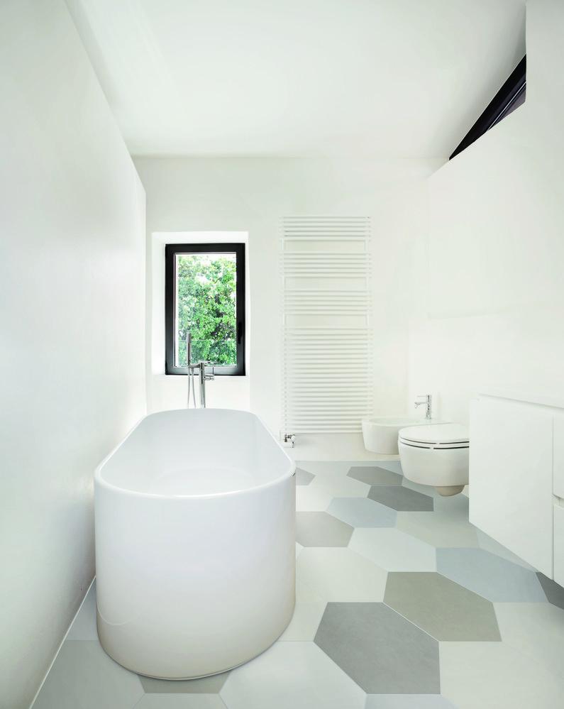 White bath rub on top of beehive tile floor