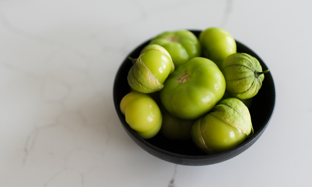 A bowl of tomatillos on a quartz countertop