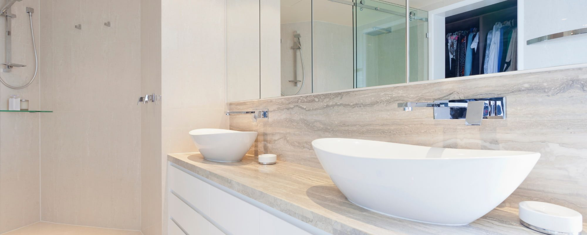 marble countertops with white sinks and a shower